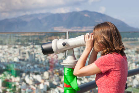 looking at viewer: Young woman is looking through the tower viewer