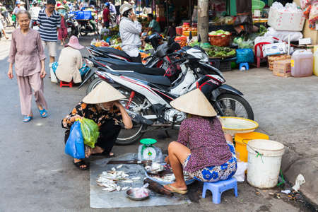 conical hat: NHA TRANG, VIETNAM - JANUARY 20: Vietnamese woman in traditional conical hat is selling fish at the wet market on January 20, 2016 in Nha Trang, Vietnam. Editorial