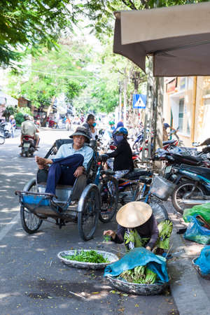 conical hat: NHA TRANG, VIETNAM - JANUARY 20: Vietnamese woman in traditional conical hat is sorting greens on the street of Nha Trang on January 20, 2016 in Nha Trang, Vietnam.