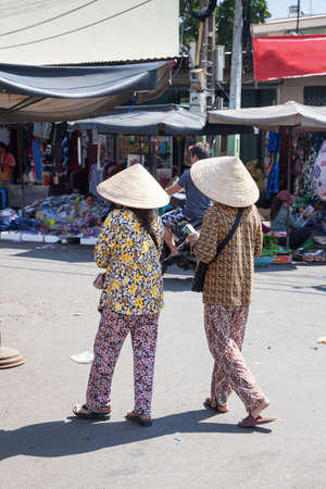 conical hat: Vietnamese women in traditional conical hat sell lottery tickets on the streets of Nha Trang, Vietnam.