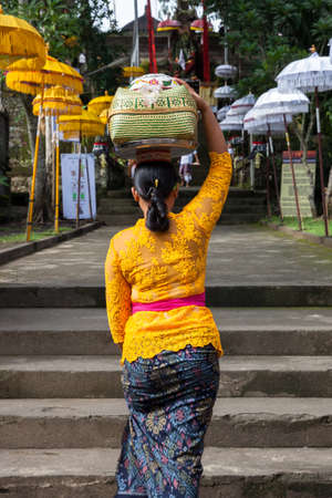 color silence: UBUD, INDONESIA - MARCH 2: Woman with basket on the head  walks up the stairs during the celebration before Nyepi (Balinese Day of Silence) on March 2, 2016 in Ubud, Indonesia. Editorial