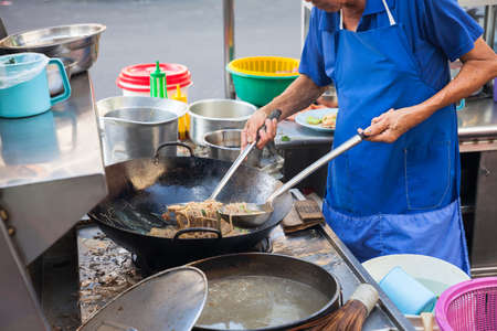 night market: Chef cooks stir-fried noodles at Kimberly Street Food Night Market. George Town, Penang, Malaysia.