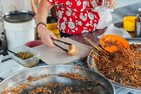 night market: GEORGE TOWN, MALAYSIA - MARCH 23: Woman packing curry puff to the plastic bag at Kimberly Street Food Night Market on March 23, 2016 in George Town, Malaysia.