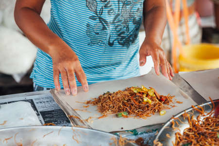 night market: GEORGE TOWN, MALAYSIA - MARCH 23: Woman packing stir-fried noodles into the paper at Kimberly Street Food Night Market on March 23, 2016 in George Town, Malaysia. Stock Photo