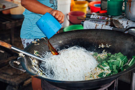 bean sprouts: GEORGE TOWN, MALAYSIA - MARCH 23: Woman cooks stir-fried noodles with bean sprouts at Kimberly Street Food Night Market on March 23, 2016 in George Town, Malaysia. Editorial