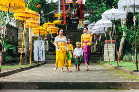 god walking: UBUD, INDONESIA - MARCH 2: Balinese family in traditional clothes during the celebration before Nyepi (Balinese Day of Silence) on March 2, 2016 in Ubud, Indonesia.
