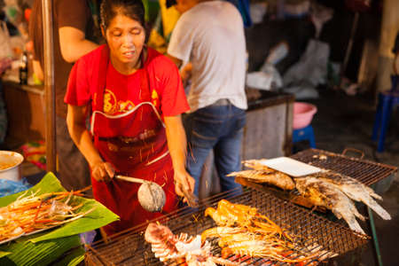 fish vendor: CHIANG MAI, THAILAND - AUGUST 27: Woman cooks prawns and squids on the grill at the Sunday Market (Walking Street) on August 27, 2016 in Chiang Mai, Thailand.