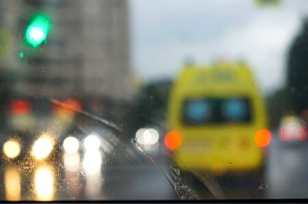 Defocused image of emergency ambulance travels through city street seeing through the wet from rain wind screen of a car. Stock Photo
