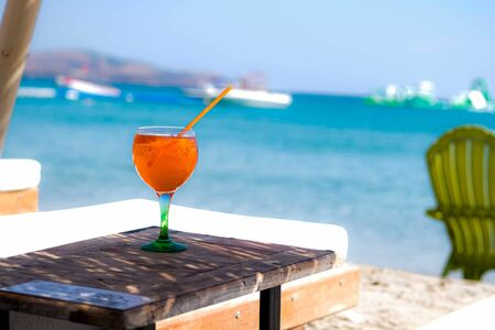 Orange drink or cocktail standing at the little table at the beach with sea background.