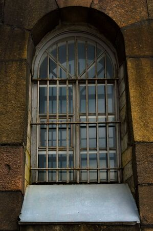 Gloomy window with grating on gray stone wall of historical building.Travel Russia, Saint Petersburg.