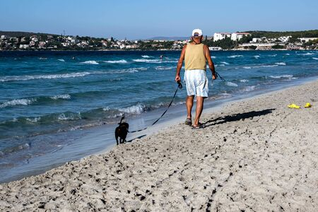 Senior man walking his dog at the beach. Cesme, Izmir, Turkey.