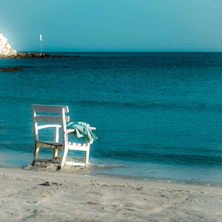Lonly shabby white chair and blue towel left at the armrest facing the blue Mediterranian sea. Solitude concept. Cesme, Izmir, Turkey. Square format.