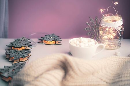 Cold autumn or winter setup. Warm cocoa with marshmellows. Cosy scene, hygge concept, top veiw. Pastel colors. Christmas is coming.