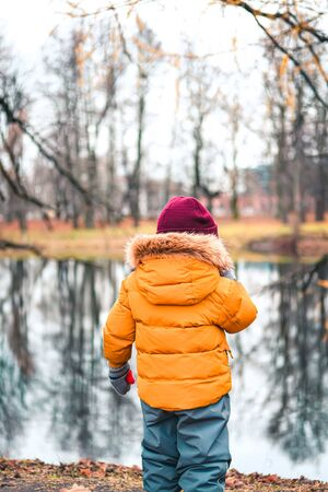 A little boy in winter cloths in late autumn or winter forest. Stock Photo