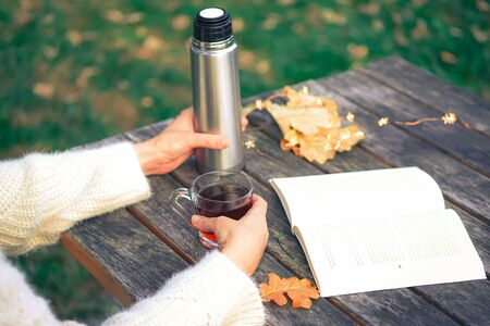 Cozy autumn tea break with a book, glasses, thermos flask,cup of tea and dry autumn leaves on old vintage wooden table. Cropped image of girls hands waring warm knitted sweater, top view.