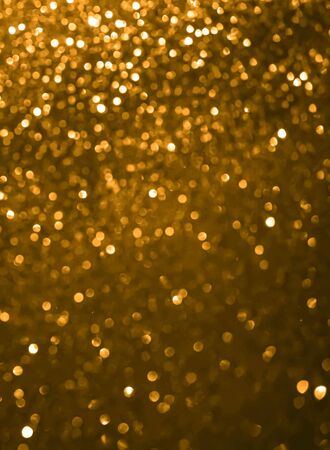 Abstract yellow saffron defocused bokeh glitter sparkle confetti burst background. Festive concept. New year, birthday, events and invitations. Vertical format.