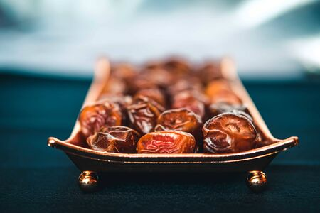 Beautiful bowl in Arabic style full of dry dates fruits symbolizing Ramadan on dark blue background.