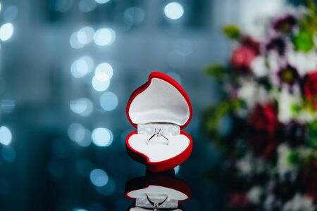 Red heart-shaped velvet box with engagement diamond ring on background with bokeh lights and flowers. Valentine background. Presents for woman on Valentines Day. Love, proposal concept.