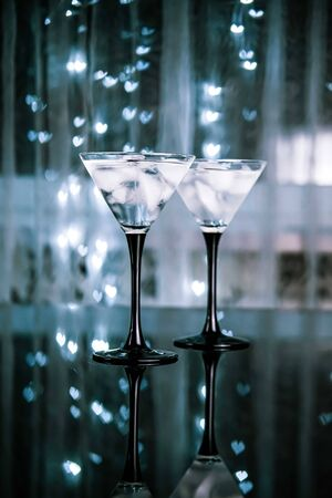 Couple of cocktail glasses with martini drink with ice on trendy black background with bokeh lights. Evening or night date concept.