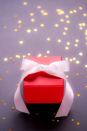 Red gift box with white ribbon on dark blue background with shining stars and hearts. Present for birthday or Christmas concept. Copy space. Vertical format. Banco de Imagens - 140726114