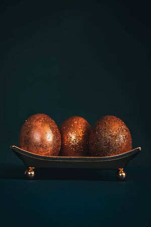 Golden or bronze decorated easter eggs on trendy black background.