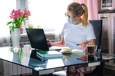 Blonde business woman working on quarantine from home on the kitchen wearing pijama and protective mask. Home office or distance learning or freelance concept.Coffee break.
