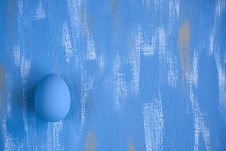 Light Blue Easter single egg on sky blue and gold canvas background. Minimalistic monochrome decoration concept.