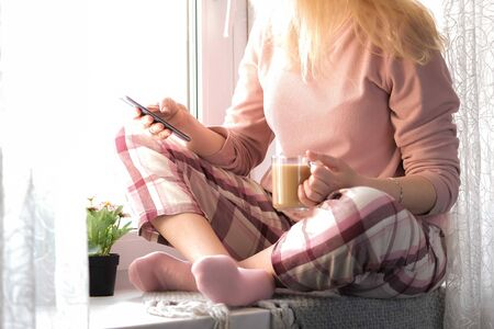 Cropped image of a blonde woman in her pijamas sitting on a window sill with a cup of coffee and her smartphone in hands. Self isolation, stay home or quarantine concept. Foto de archivo