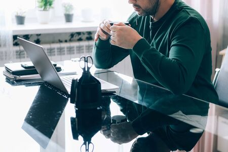 Cropped image of a handsome businessman with eyeglasses and stubble working remotely from home at his laptop computer and drinking coffee. Foto de archivo