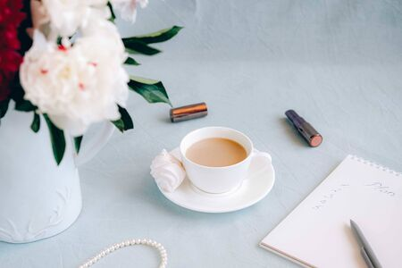 Morning coffee with flowers, spiral notebook and some feminine accessories. Modern womans morning concept. Imagens