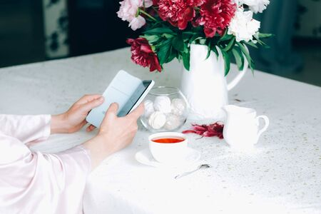 Cropped image of a woman, holding a smartphone in light blue case, reading the news, over a cup of tea, Beautifully styled tea scene with white tablecloth, bouquet of pink peony flowers. Gadget addict concept.