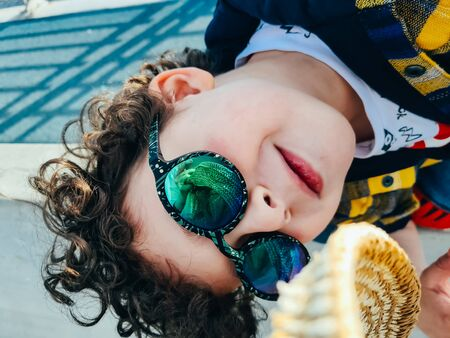 Funky stylish cool little boy with curly hair in trendy sunglasses smiling and having fun in sunny summer day. Youth fashion concept.
