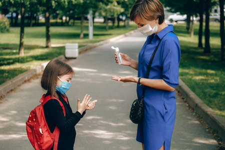Mother wearing protective face mask applies sanitizer for cleaning her daughters hands in public place. New normal, back to school, resilience concept.