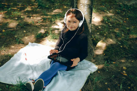 happy girl in white headphones using digital tablet pc in the park. Distant learning concept. Resilience, back to school, new normal.