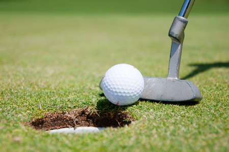 golf hole with ball and putt photo