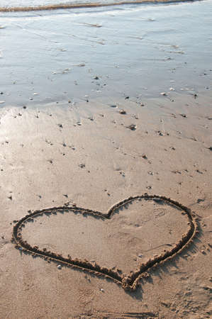 heart drawn in the sand on the beach