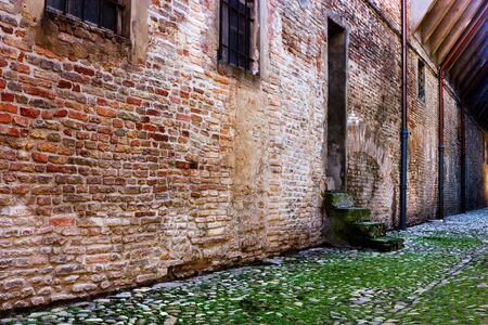 dirty alley in the old town with pavement of porphyry cobblestones photo
