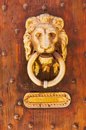 old knocker of brass on wooden door with studs and slot for mail  photo