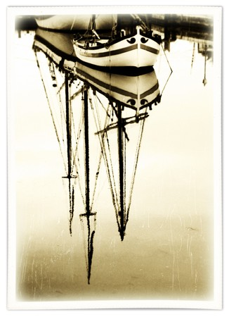 photo of a reflex on the water of old sailboats in the harbour - photography   with retro look effect photo