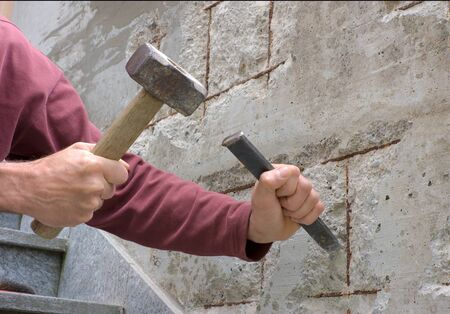 chisel: mason with chisel and hammer restores the concrete where the metal is rusty