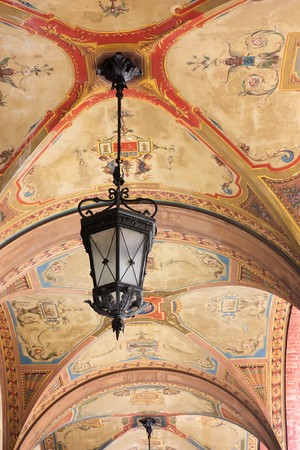 ceiling of the arched portico decorated with fresco - ancient paintings and lamp   on the vault of the porch photo