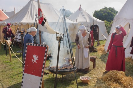 cooked meat: medieval camp, scenes of antique daily life, girls cooked meat on the grill, party devoted to the historical reenactors - festival