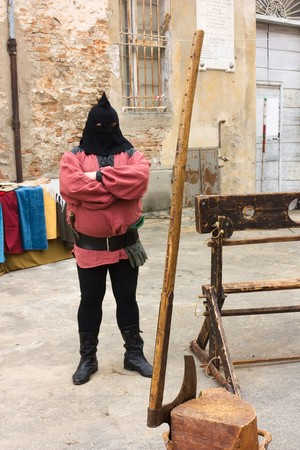FAENZA, RA, ITALY - NOVEMBER 7: executioner with pillory, axe, execution block . Historical re-enactment in