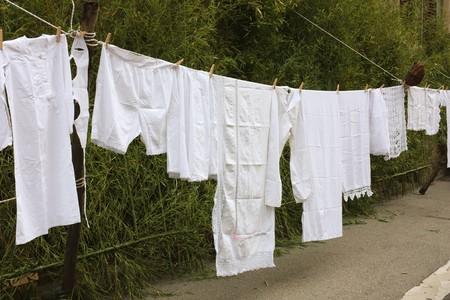 ropa colgada: ropa interior antigua colgando a seco - bloquea fuera el lavado - ropa-l�nea con ropa de cama antigua  Foto de archivo