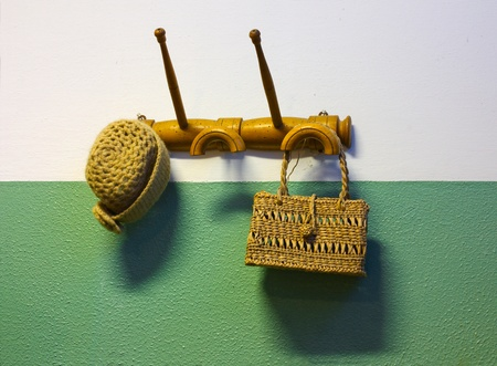 old hanger with hat of rope and handbag of wicker - coat hook on retro style painted wall  photo