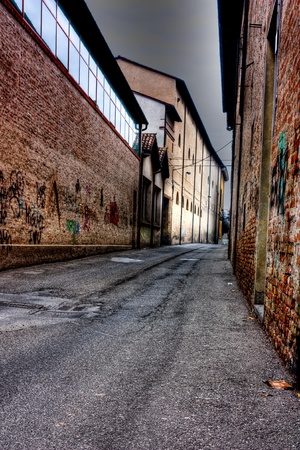 street in the twilight, night is falling in the decadent old town, grunge dark alley at dusk, evening in slums of the city, urban decay Stock Photo