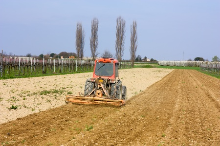 harrow: farmed land view - harrow for soil preparation - field with agricultural tractor preparing the ground for sowing  Stock Photo