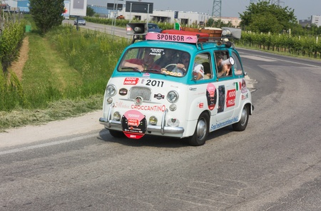 FORLI, ITALY - MAY 13: unidentified crew drive a Fiat 600 Multipla of the sponsoring company in stage Bologna-Roma of the Mille miglia historical race for classic cars, on May 13 2011 in Forli, Italy