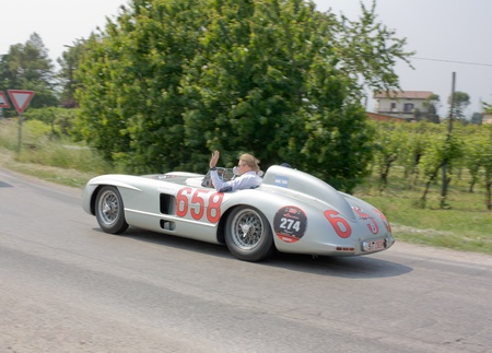 FORLI, ITALY - MAY 13: Mika Hakkinen and Juan Manuel Fangio drives a Mercedes-Benz 300 SLR (1955) in stage Bologna-Roma of the Mille miglia historical race for classic cars, on May 13 2011 in Forli, Italy