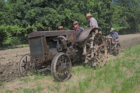 BASTIA, RAVENNA, ITALY - MAY 29: unidentified men plow the land with an old tractor during ricordando i vecchi tempi recall of the old farm work, on May 28-29 2011 in Bastia, Ravenna, Italy